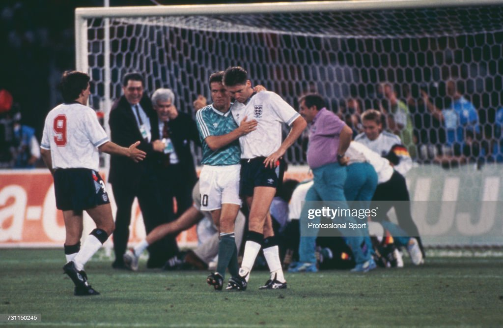German footballer and captain of the West Germany team, Lothar Matthaus (#10) puts his arm around English footballer Chris Waddle (#8) as teammate Peter Beardsley (#9) offers support after Waddle failed to score for England to allow West Germany to beat England 4-3 in the penalty shoot out to settle the semi final match in the 1990 FIFA World Cup at the Stadio delle Alpi in Turin, Italy on 4th July 1990. The match would end 1-1 after extra time with West Germany winning the penalty shoot out 4-3 to progress to the final.