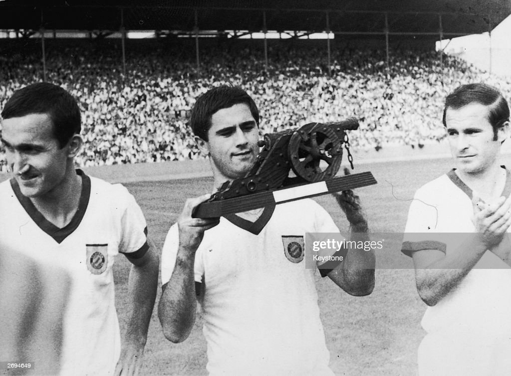 German footballer Gerd Muller examining a presentation model cannon. Muller went on to score sixty-eight goals in sixty-two games for West Germany.