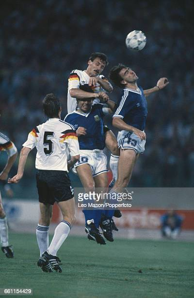German footballer Klaus Augenthaler looks on as teammate Juergen Kohler leaps for the ball with Diego Maradona and Nestor Lorenzo of Argentina during...