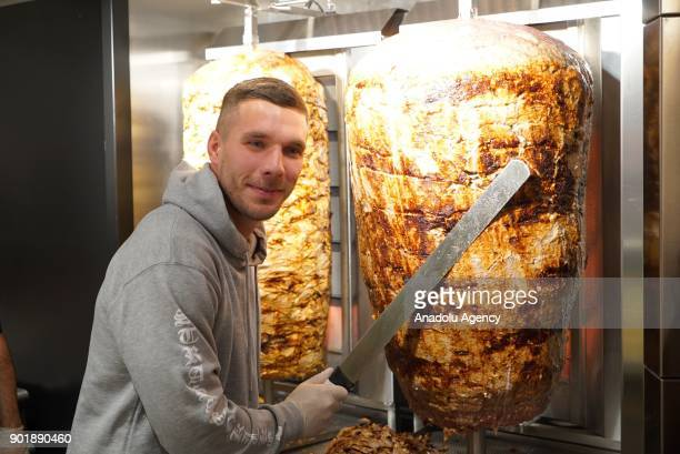 German footballer Lukas Podolski poses for a photo with a doner knife as he opened up a Doner Kebab Restaurant called Mangal Doner with two other...