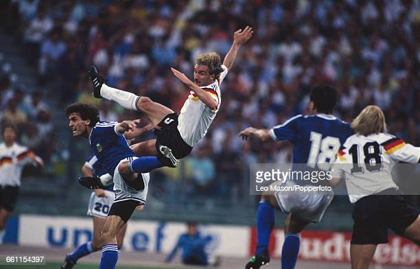 German footballer Rudi Voller leaps in the air as he tussles with Oscar Ruggeri of Argentina as Jose Serrizuela and Jurgen Klinsmann look on during...