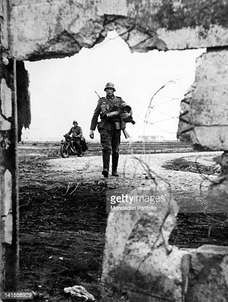 A German footman and a motorcyclist advancing toward a breach in a Polish defence near Warsaw Poland September 1939