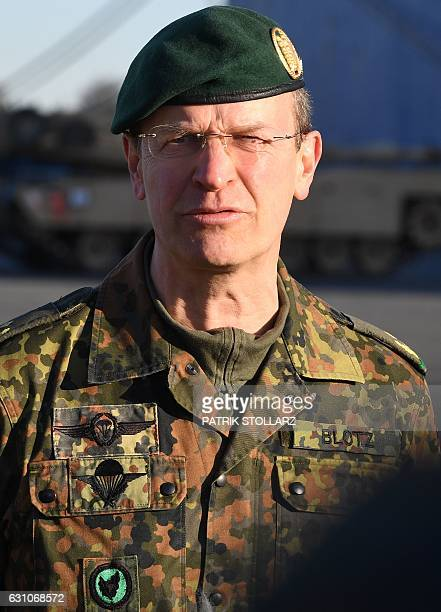 German Force commander General Major Josef Dieter Blotz is pictured as US military vehicles are unloaded from a carrier ship in the harbour in...