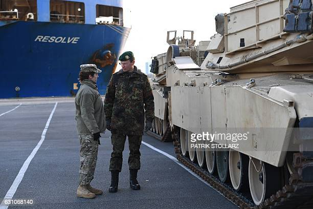 German Force commander General Major Josef Dieter Blotz talks to a US military service personel as US military vehicles are unloaded from a carrier...