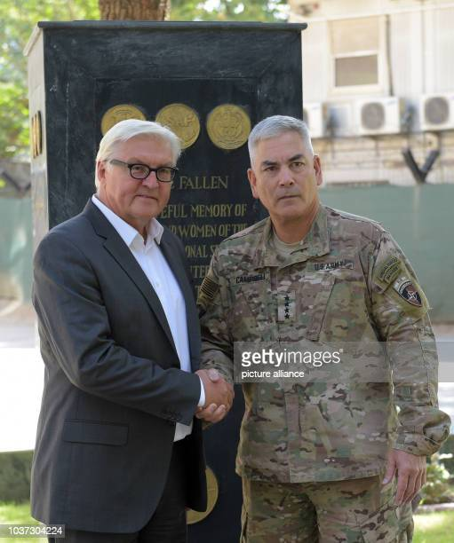 German Foreign Minister FrankWalter Steinmeier shakes hands with commander of the Resolute Support Mission General John F Campbell in the...