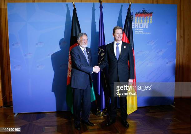 German Foreign Minister Guido Westerwelle and Afghan Foreign Minister Zalmay Rassoul shake hands at an informal meeting of NATO member foreign...