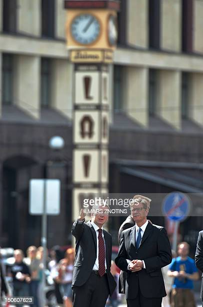 German Foreign minister Guido Westerwelle and his Latvian counterpart Edgars Rinkevics speak near the Monument of Freedom in Riga on August 23, 2012....