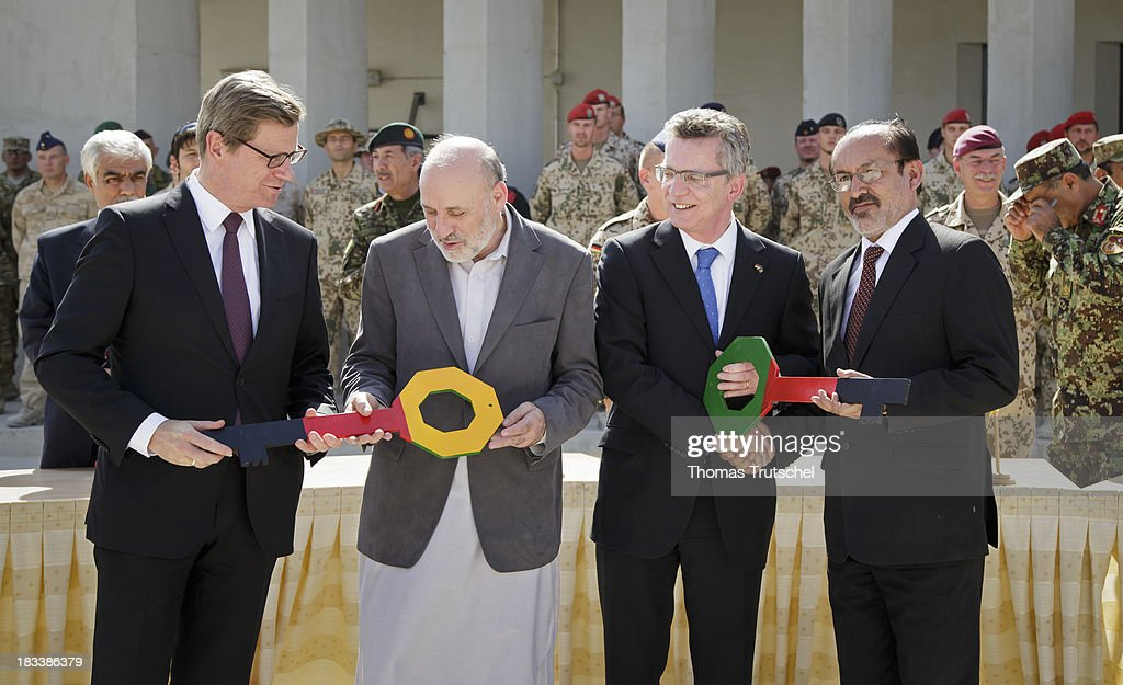 German Foreign Minister Guido Westerwelle, Omar Daudzai, Afghan Interior Minister, German Defence Minister Thomas de Maiziere, and Bismullah Khan Mohammadi, Afghan Defence Minister during a handover of symbolic keys on October 06, 2013 in Kunduz, Afghansitan. Westerwelle and de Maiziere visit Afghanistan to hand over German PRT in Kunduz to the Afghan Military.