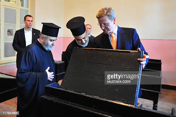 German Foreign Minister Guido Westerwelle speaks with Orthodox priest father Dositeos at the Holy Trinity Monastery at Halki Island one of the...