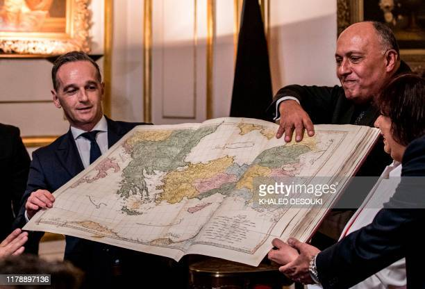 German Foreign Minister Heiko Maas and his Egyptian counterpart Sameh Shoukri pose for a picture with a recovered historical atlas that was...
