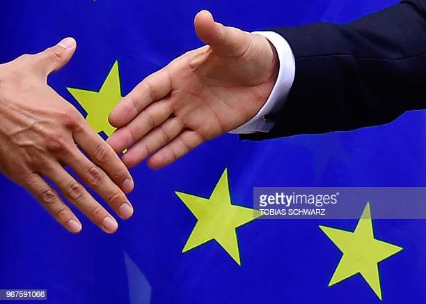 German Foreign Minister Heiko Maas and his Hungarian counerpart Peter Szijjarto shake hands in front of a European flag following a joint press...