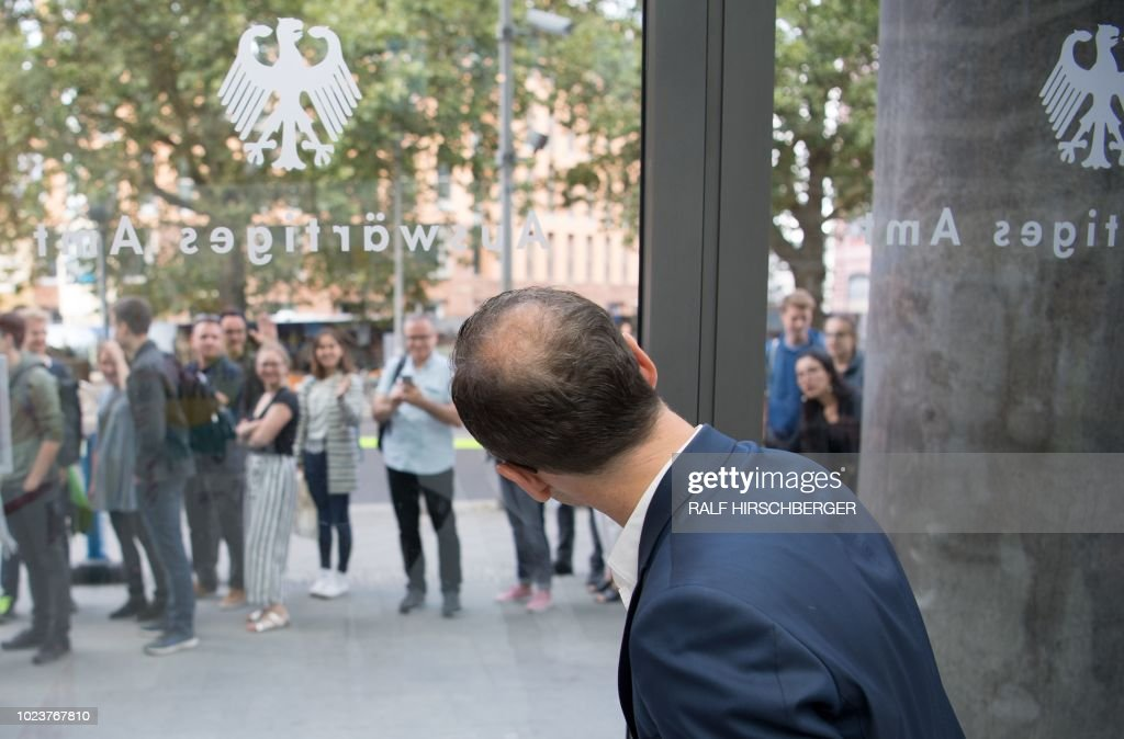 German Foreign Minister Heiko Maas looks out of a window of the Foreign Ministry in Berlin, where visitors line up to get access during an Open Day of the German government on August 26, 2018. (Photo by Ralf Hirschberger / dpa / AFP) / Germany OUT