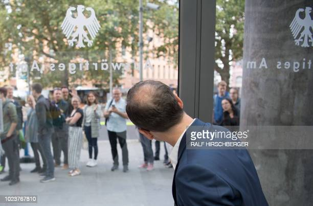 German Foreign Minister Heiko Maas looks out of a window of the Foreign Ministry in Berlin where visitors line up to get access during an Open Day of...