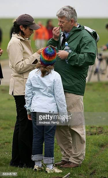 German Foreign Minister Joschka Fischer and his girlfriend Minu Barati with her child taste a flower called Queller during their walk through...