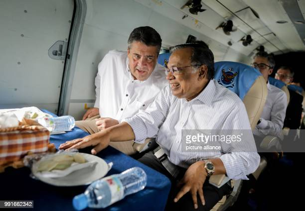 German Foreign Minister Sigmar Gabriel speaks with his Bangladeshi counterpart Abul Hassan Mahmud Ali onboard a helicopter taking them to the...