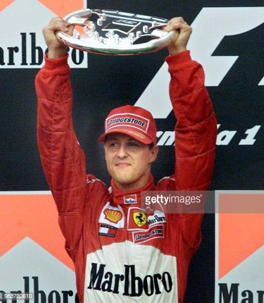 German Formula One driver Michael Schumacher his second place Brazilian Formula One GP trophy 01 April 2001 in Sao Paulo Brazil Coulthrad won...