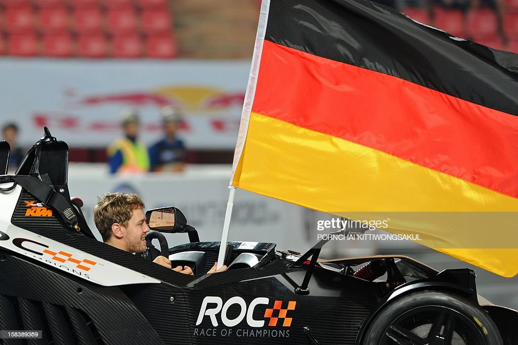 German Formula One World Champion Sebastian Vettel holds his national flag during the Race of Champions (ROC) Nations Cup Drivers 's Presentation at Rajamangala Stadium in Bangkok on December 15, 2012. The Race of Champions (ROC) will take place in Thailand between December 14 and 16 and brings together heavyweights from all motor racing disciplines in the same type of car.
