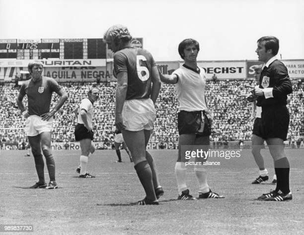 German forward Gerd Mueller backslaps English defender Bobby Moore in comfort after Moore was cautioned by the Argentine referee Angel Norberto...
