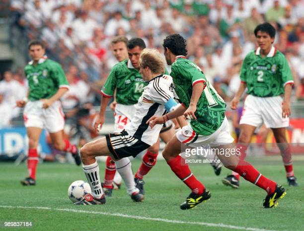 German forward Juergen Klinsmann falls to the ground but manages to score the 1-1 equalizer while the Mexican defenders cannot intervene during the...