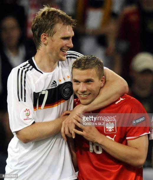 German forward Lukas Podolski, wearing the jersey of Polish midfielder Mariusz Lewandowski and teammate defender Per Mertesacker celebrate at the end...