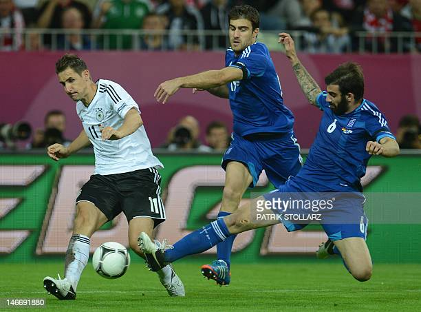 German forward Miroslav Klose vies with Greek defender Sokratis Papastathopoulos and Greek midfielder Grigoris Makos during the Euro 2012 football...