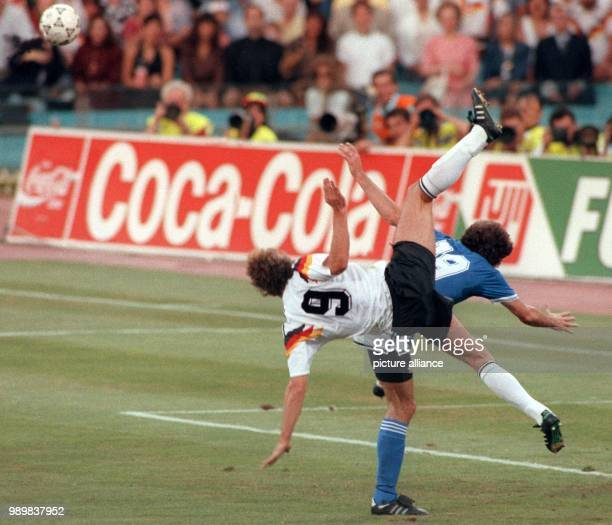 German forward Rudi Voeller and his Argeninean opponent Oscar Ruggeri seem to perform a pirouette as they fight for the ball The German national team...