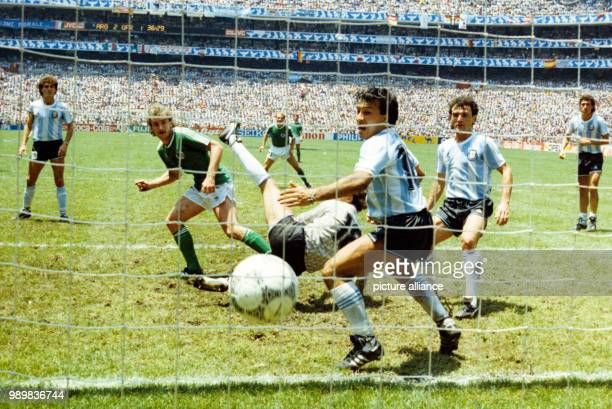 German forward Rudi Voeller scores the 22 equalizer with a header while the Argetine goalkeeper Nero Pumpido falls to the ground and the Argentine...