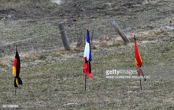 German French and Spanish flags fly on March 25 2015 in a field in the southeastern French village of Le Vernet the closest to the site where the...