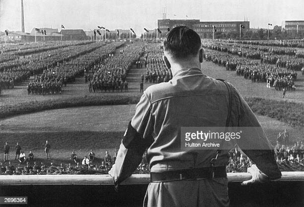 German Fuhrer and Nazi leader Adolf Hitler addresses soldiers with his back facing the camera at a Nazi rally in Dortmund Germany