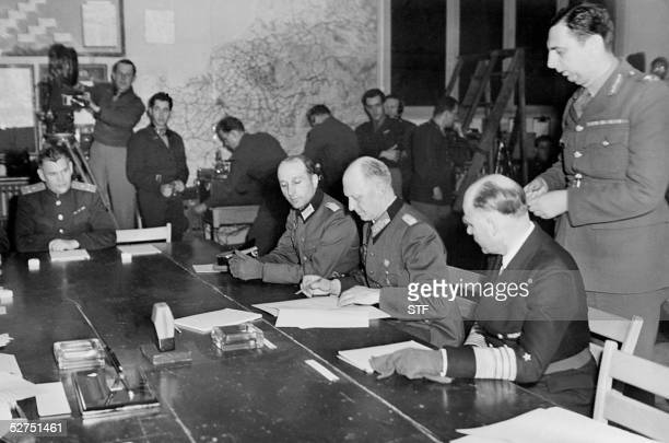 German General Alfred Jodl flanked by Admiral Von Friedeburg signs 07 May 1945 the German surrender document at the Allied headquarters in Reims...