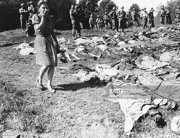 German girl is overcome as she walks past the exhumed bodies of some 800 slave workers killed by SS guards May 17 1945 near Namering Germany Bodies...