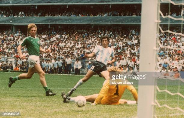 German goalie Harald Schumacher is beaten by Argentinian forward Jorge Valadano as he shoots the ball past Schumacher and scores the 20 while German...