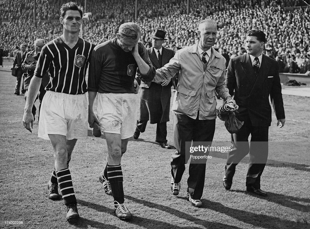 German goalkeeper Bert Trautmann (1923 - 2013, second from left), of Manchester City FC, leaves the field with an injured neck at the end of the FA Cup Final against Birmingham City at Wembley Stadium, London, 5th May 1956. Trautmann had been injured in a collision with Birmingham's Peter Murphy 17 minutes from the end of the match, but continued to play, making saves, which enabled his team to maintain their 3-1 lead and win the cup. Medical examination later revealed that Trautmann had been playing with a broken neck.