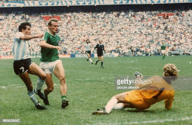 German goalkeeper Harald Schumacher rushes out of his goal to meet attacking Argentinean forward Jorge Burruchaga who albeit being also attacked by...