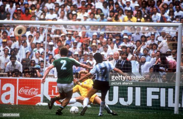 German goalkeeper Harald Schumacher rushes out of his goal to meet attacking Argentinian forward Jorge Burruchaga who albeit being also attacked by...