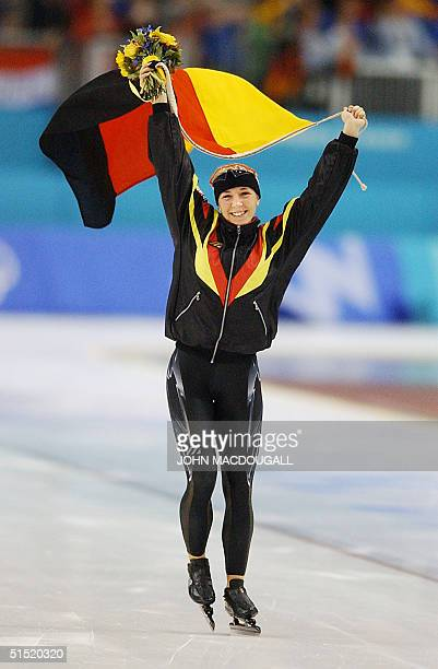 German gold medalist Anni Friesinger takes a honour lap with her national flag after winning the women's 1500m speed skating race at the Utah Olympic...