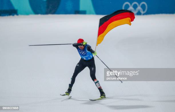 German gold medallist Johannes Rydzek waves the German flag as he crosses the finish line of the men's team large hill/4 x 5 km Nordic combined event...
