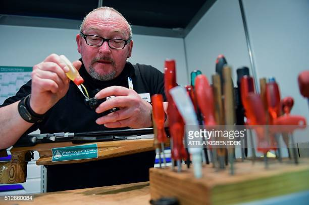 A German gunsmith fixes a sight of a rifle in AUDI Arena of Gyor on February 26 2016 after the qualification round of 10m air rifle category for...