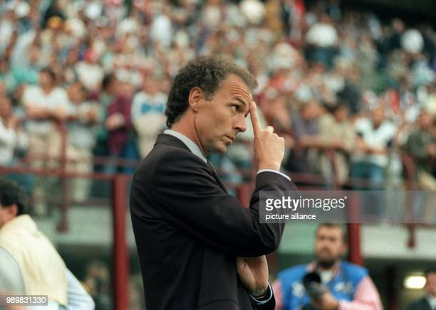 German head coach Franz Beckenbauer scratches his forehead as he observes the performance of his players on the pitch during the 1990 World Cup group...