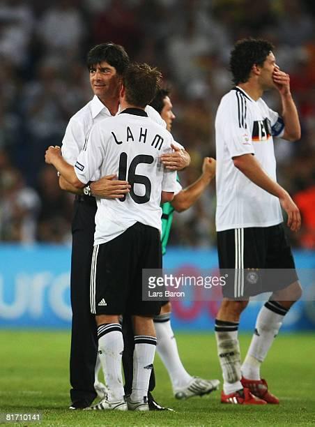 German head coach Joachim Loew embraces defender Philipp Lahm while Michael Ballack walks on after the UEFA EURO 2008 Semi Final match between...