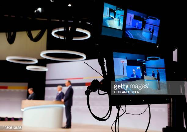 German Health Minister and Christian Democratic Union politician Jens Spahn appears on a screen as he intervenes while the three candidates as leader...