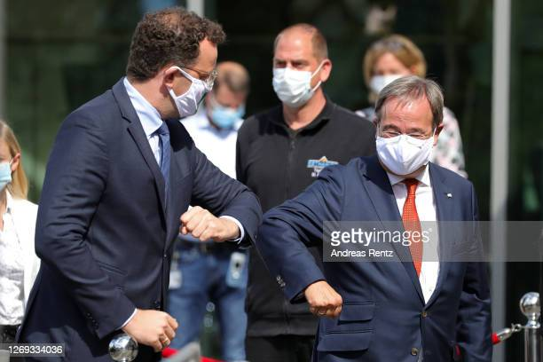 German Health Minister Jens Spahn greets North Rhine-Westphalia Governor Armin Laschet by bumping their ellbows ahead of a visit to a tent used for...