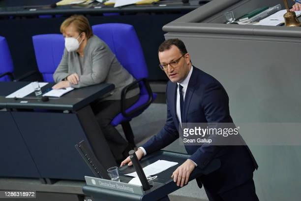 German Health Minister Jens Spahn speaks as Chancellor Angela Merkel looks on during debates at the Bundestag on modifications to a law called the...
