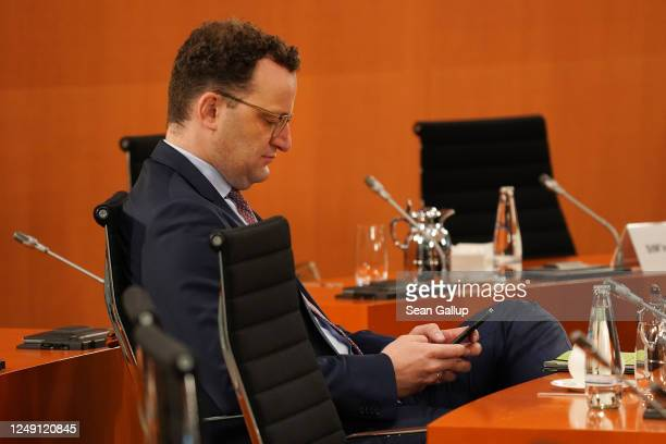 German Health Minister Jens Spahn uses a smartphone prior to a meeting of the German government cabinet during the coronavirus pandemic on June 12...