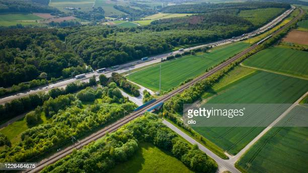 german highway and highspeed train railroad track - aerial view - high speed train stock pictures, royalty-free photos & images
