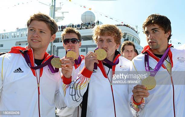German hockey Olympic gold medal winners Matthias Witthaus JanPhilipp Rabente and Tobias Hauke show their gold medals at the port of Hamburg northern...