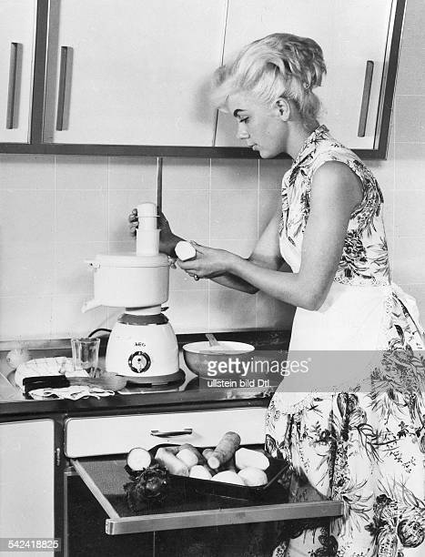 German housewife wearing a petticoat dress and squeezing vegetable juice with an AEG kitchen food processor 1958 Also available in color Image Number...