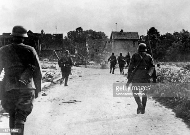 German infantry detachment going among the ruins of an Alsatian village during the World War II. Alsace, June 1940