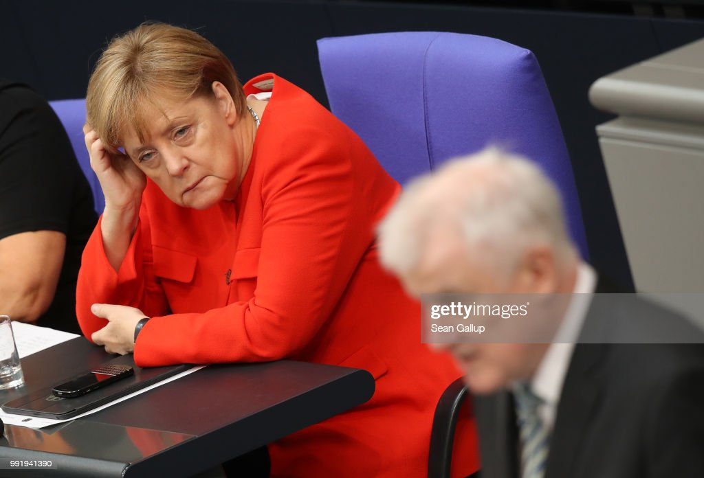 German Interior Minister and leader of the Bavarian Social Union (CSU), Horst Seehofer, speaks at the last session of the Bundestag before the sumer break as German Chancellor and leader of the German Christian Democratic Union (CDU) Angela Merkel (in red) looks on on July 5, 2018 in Berlin, Germany. Merkel and Seehofer recently reached a hard-wrung compromise over migration policy, though uncertainty remains over how the compromise will be implemented.