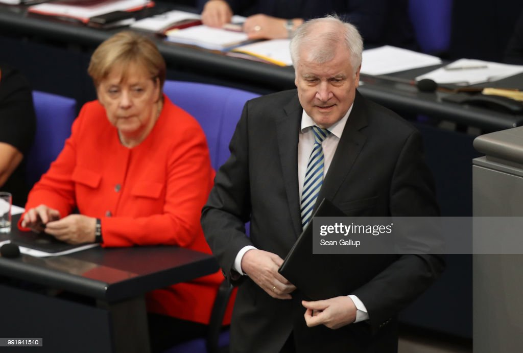 German Interior Minister and leader of the Bavarian Social Union (CSU), Horst Seehofer, prepares to speak at the last session of the Bundestag before the sumer break as German Chancellor and leader of the German Christian Democratic Union (CDU) Angela Merkel looks on on July 5, 2018 in Berlin, Germany. Merkel and Seehofer recently reached a hard-wrung compromise over migration policy, though uncertainty remains over how the compromise will be implemented.